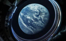 Earth planet in space ship window porthole. Elements of this image furnished by NASA. Earth planet and astronaut in space ship porthole. Elements of this image Royalty Free Stock Photography