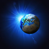 Earth planet in sun rays Stock Photos