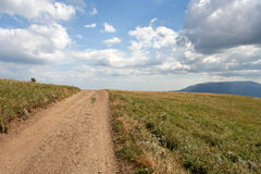 The earth-road, the distant mountain, the field with green grass and the sky with clouds. Royalty Free Stock Images