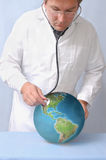 Earth's condition diagnosis. Male doctor examining Earth's condition with stethoscope Stock Images