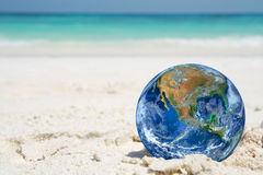 The earth on sand beach, including elements furnished by NASA Royalty Free Stock Photography