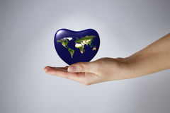 The Earth in the shape of heart in a female hands Royalty Free Stock Photography