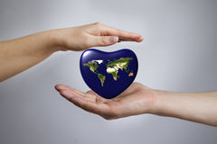 The Earth in the shape of heart in a hands Stock Images