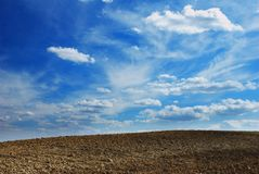 Earth and sky. Stunning cloudy background over plowed land royalty free stock image