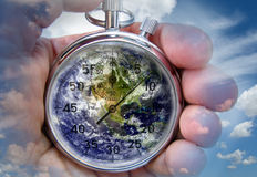 Earth time. Hand holding chronometer with planet earth, time running out concept Stock Image