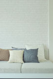 Earth tone color pillows on sofa with white brick wall. In background stock photos