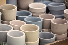 Earth tone colored clay flowerpots. Stack of earth tone colored clay flowerpots displayed in a wooden rack royalty free stock images
