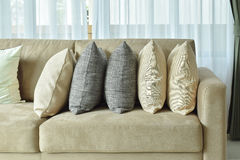 Earth tone pillows setting on light brown sofa in the living room Royalty Free Stock Image