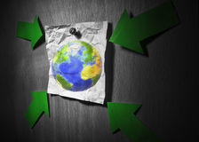 Earth topic. Conceptual environment image. Earth pined to wall on a crumpled paper and pointed by green arrows. Earth is a garbage concept. Some graphics in this Stock Photography