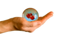 Earth with two hearts in hand. Blue glass earth with two red hearts in the woman hand Stock Photos