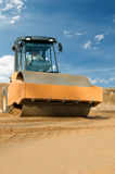Earth vibration compactor at work. Soil vibration roller during sand compacting works at construction road site Stock Images
