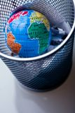Earth in waste-bin. Conceptual image about saving Earth. The globe droped and left  in a waste-bin Stock Photos