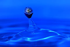 Earth within a water drop. Stock Photos