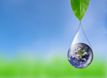 Earth in water drop reflection green leaf, Elements of thi. Earth in water drop reflection under green leaf, Elements of this image furnished by NASA Royalty Free Stock Images