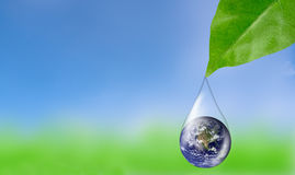 Earth in water drop reflection under green leaf. Royalty Free Stock Photography