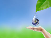 Earth in water drop reflection under green leaf hold hand. Royalty Free Stock Photos
