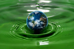 Earth in water ripples. Planet Earth floating over green water, environment concept Royalty Free Stock Photo