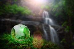 Earth World Globe Crystal on water fall Royalty Free Stock Images