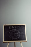 Earth written on blackboard with earth symbol, background, high Royalty Free Stock Photo