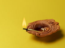 An earthen indian lamp. On yellow background Royalty Free Stock Images