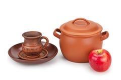 Earthen pot, jug, plate and ripe apple Stock Photos