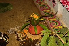 earthen pot and mango leaves with floral decoration stock images
