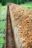 Earthen trench. Long earthen trench dug to lay pipe Stock Photo
