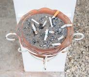 Earthenware ashtray with the cigarette stub. Stock Photos