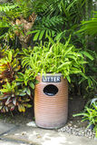 Earthenware litter bin with green plant Stock Photography