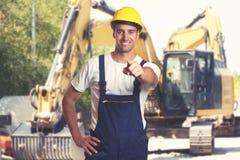 Earthmover με την υπόδειξη του λατινοαμερικάνικου εργάτη οικοδομών στοκ εικόνες με δικαίωμα ελεύθερης χρήσης
