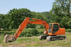 Earthmover. Orange digger standing idle in a field with trees and a blue sky to the rear Stock Images