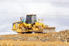 Earthmover. Large yellow earthmover moving rocks in Quarry Stock Photo
