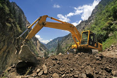 Earthmover bulldozer in himalayas clearing landslide. Landslide and heavy earth moving machinery Stock Photo