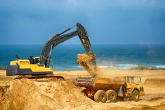 Earthmover loads the ground in the truck. At the road construction Stock Photography