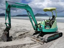 Earthmoving equipment: excavator on beach royalty free stock images