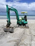Earthmoving equipment: excavator on beach - front Royalty Free Stock Image