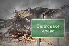 Earthquake Ahead. A view of a house distroyed by an earthquake with a sign of Earthquake Ahead stock photos
