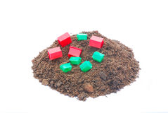 Earthquake concept. A big heap of plain brown soil with lots of little fallen green and red plastic houses on top. Image isolated on white studio background Stock Photos