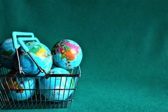 Earths globe in shopping cart. Earth globe in shopping cart. How many Earths do we need royalty free stock photo