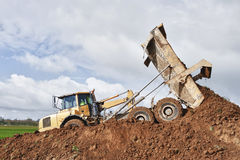 Earthwork. Earth mover dumping earth on a hill Stock Images