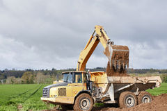 Earthwork. Earth mover dumping earth on a hill Royalty Free Stock Images