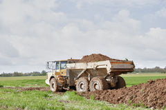 Earthwork. Earth mover dumping earth on a hill Stock Photography