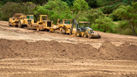 Earthwork Site and Equipment. Bulldozers, graders and backhoes parked at a grading project site Royalty Free Stock Image