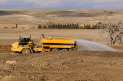 Earthwork smoothing water sprayer Royalty Free Stock Photo