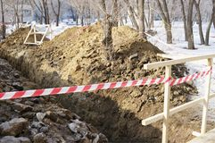 Earthworks.Dug trench and fence tape. Royalty Free Stock Image