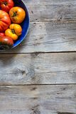 Earthy halved plate of colored cracked heirloom tomatoes over wood Stock Images