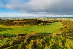 Eary morning light reveals a lush green golf course with a rolling landscape of grass and fields in Ireland stock photos