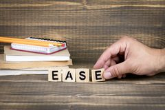 Ease. Wooden letters on the office desk. Informative and communication background royalty free stock image