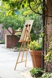 Easel με το σημάδι ή ζωγραφική μπροστά από το κτήριο τούβλου δίπλα στις σε δοχείο εγκαταστάσεις στον κήπο Στοκ Εικόνες