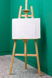 Easel. Wooden easel with blank canvas in front of a green wall Royalty Free Stock Image